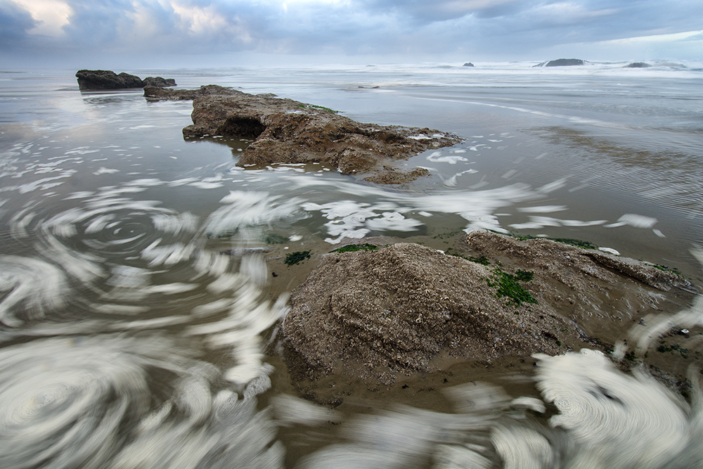Swirling sea foam in the morning tide Oregon coast
