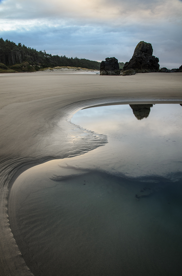 Calm sunrise reflected in glassy tide pool Oregon