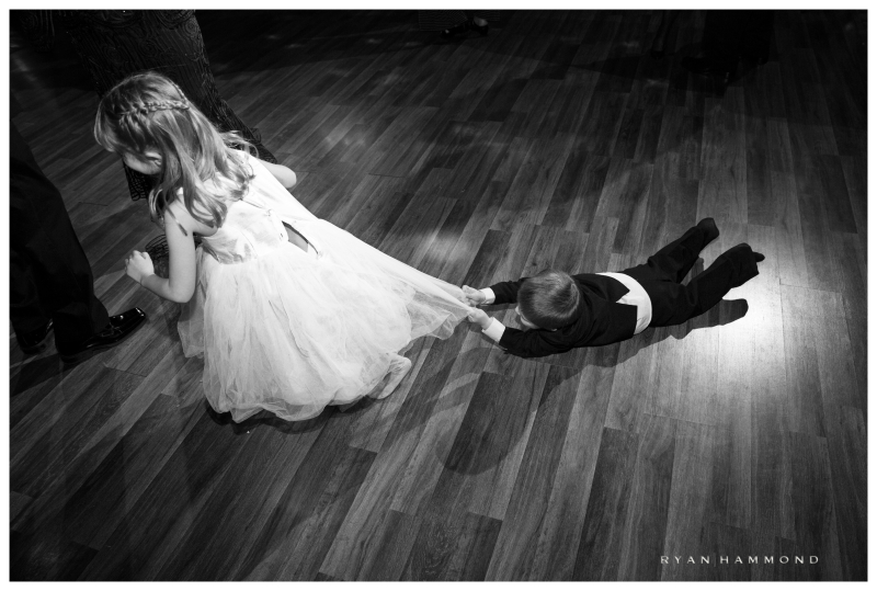 Towards the end of this wedding that I recently photographed, I kept watching this little Ring Bearer having the time of his life chasing the Flower Girl.  Then this happened, perfectly capping the end of the night.  He actually held on for several seconds as she playfully dragged him behind over the polished wooden dance floor.