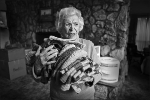 98 year-old Joan Mazzarelli with caps she knitted