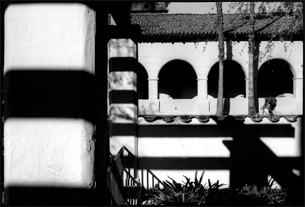 A bike rider moves past the San Fernando Mission