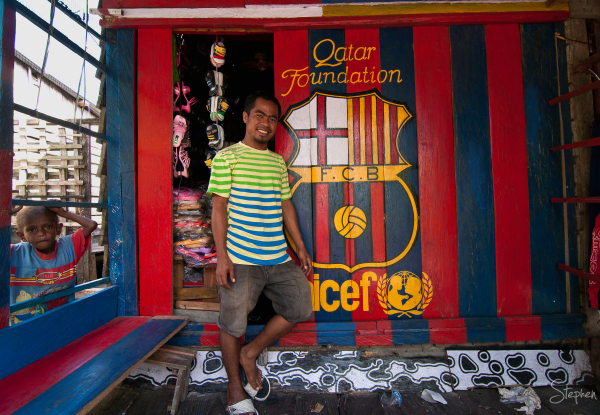 Barcelona football fan and his shop front in Agats