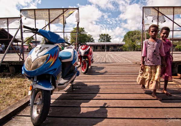 Electric motor bikes on the boardwalk in Agats