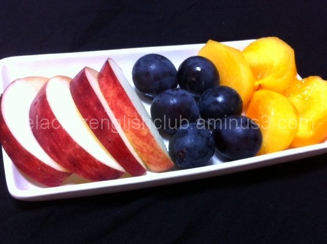 A platter of fruits (Apples, grapes and persimmon)