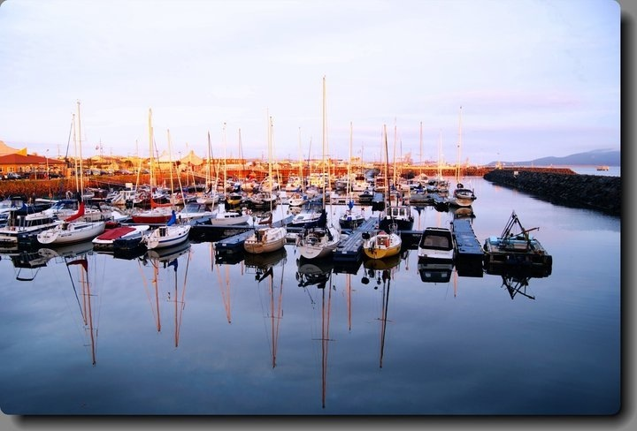 mirror image of a sunset in a marina
