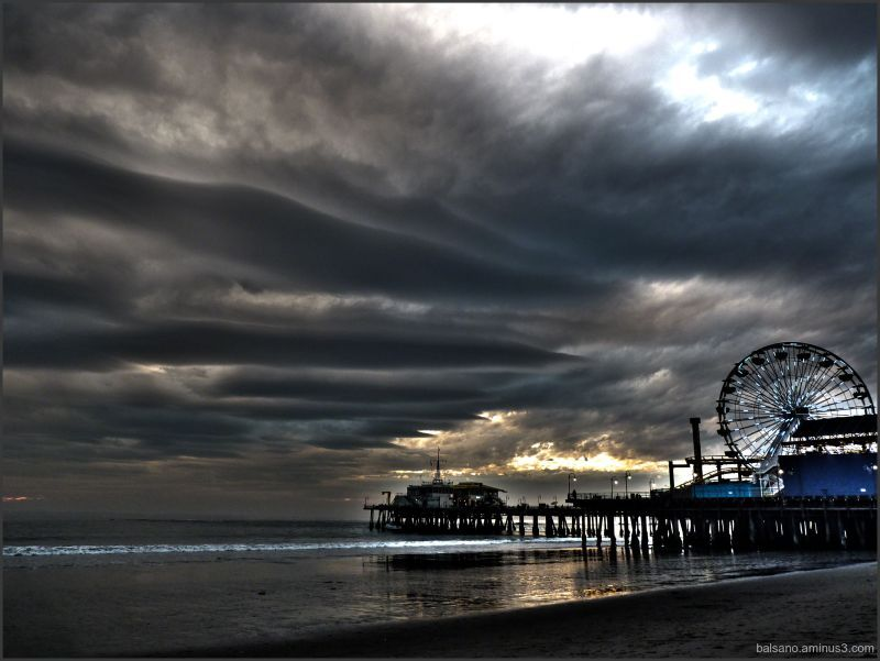 Greetings from Santa Monica, California, USA  Santa Monica Pier is in Santa Monica California.   I have lived on this beach or blocks from this beach for 30 years.    It is home.    The sea and sky are raging full of life, changing colors from day to day.   On this rare storm day the clouds gathered in a most beautiful and dramatic way.