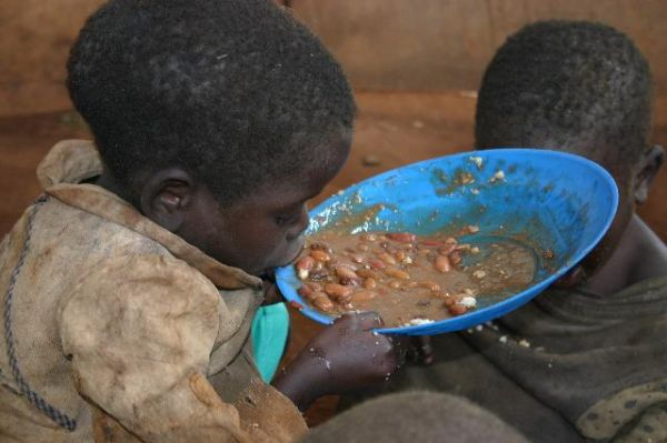 Young pygmie boy eating beans - hunger in Muyinga
