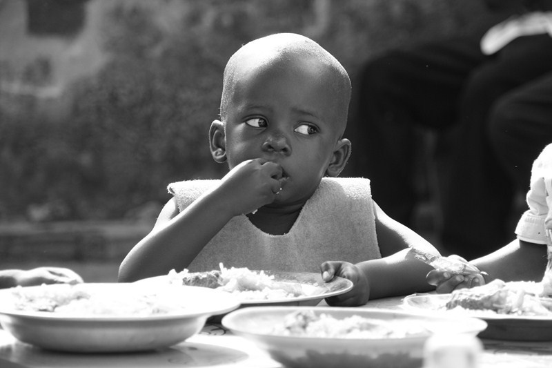 Young Burundian girl eating rice