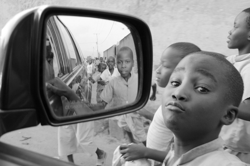 Pupils in Burundi running around a car