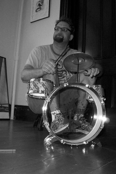 A photograph of the artist playing drums.