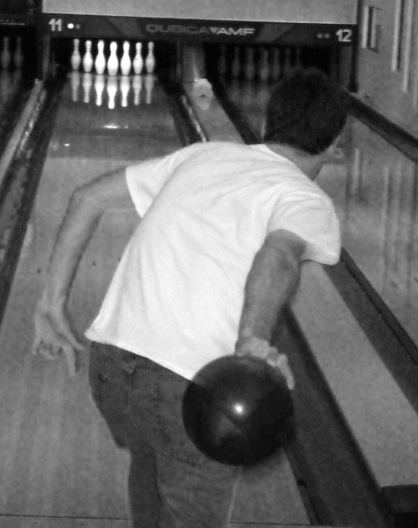 A photograph of Justin bowling.
