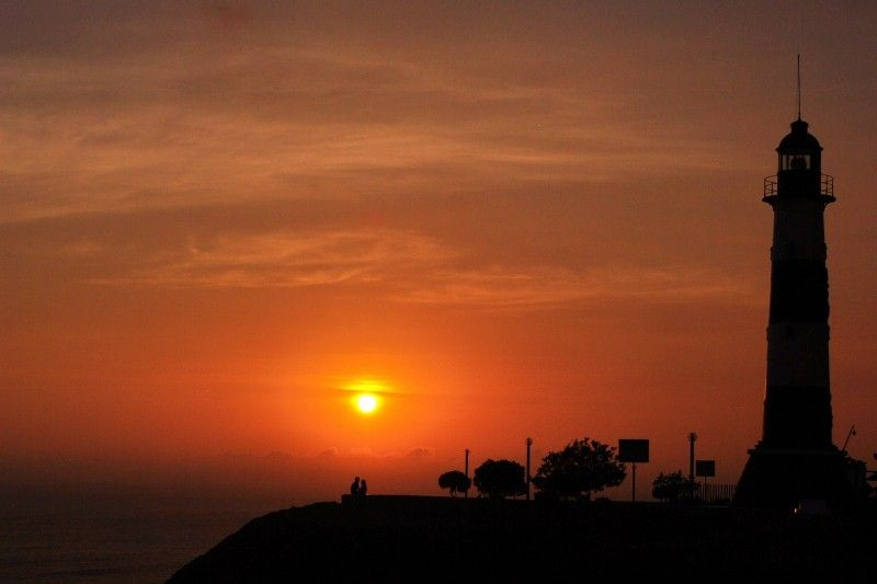 a couple caught in embrace just as the sun sets on the malecon Miraflores