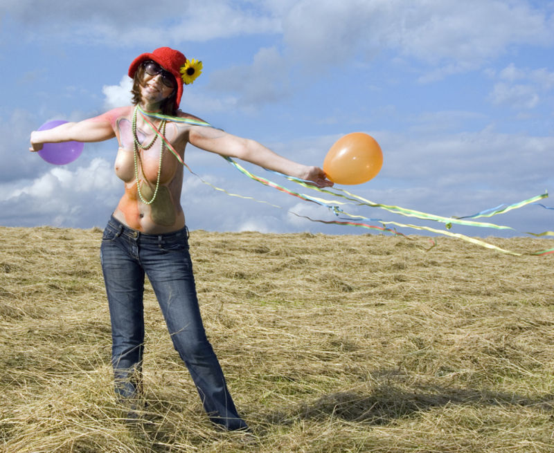 semi-nude girl with balloons on stormy field