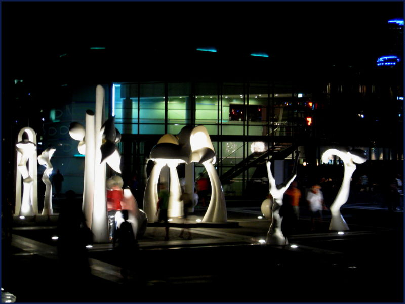 statues with people walking at Docklands at night