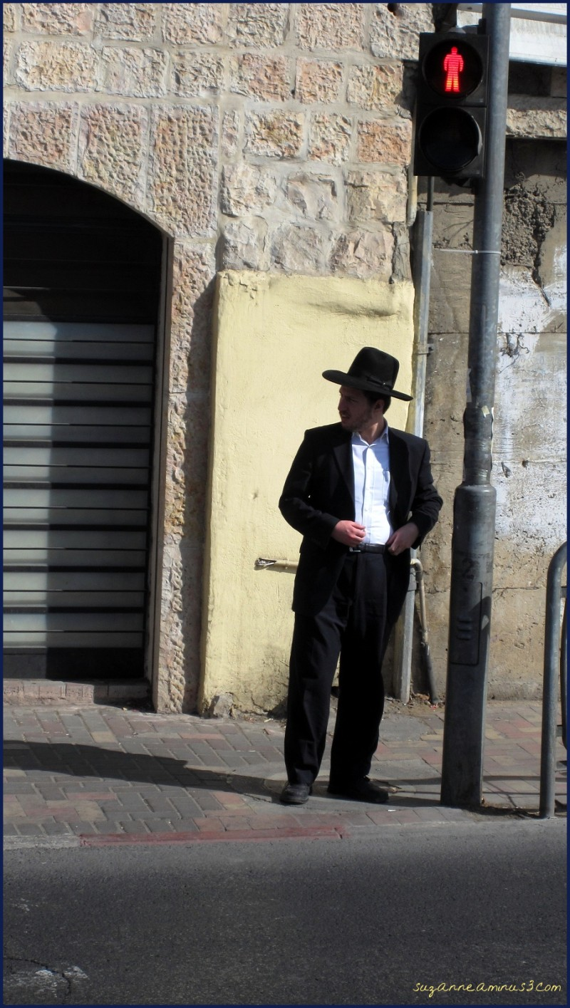 an Orthodox Jewish man standing at a red crossing