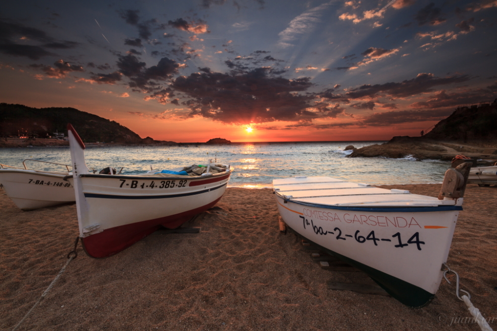 Rising Sun on the beach with two boats