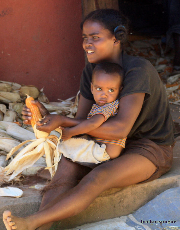 Malagasy women prepares corn with her child.