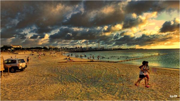 Two girls walk along the beach.