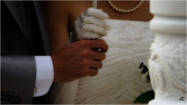 Two hands in unity ring the wedding bells.