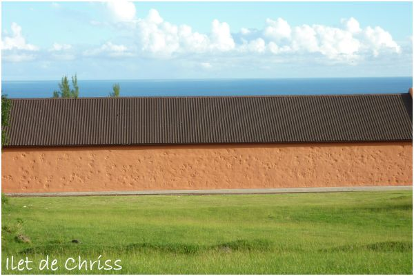 Long bâtiment entre mer et herbe