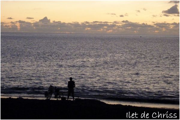 Un pêcheur et son vélo après le coucher du soleil