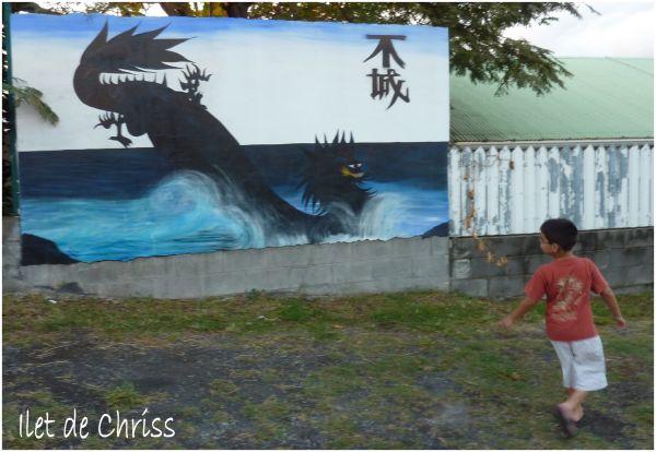 Un enfant regarde un monstre peint sur un mur