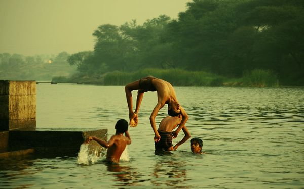 Boys somersaulting in water