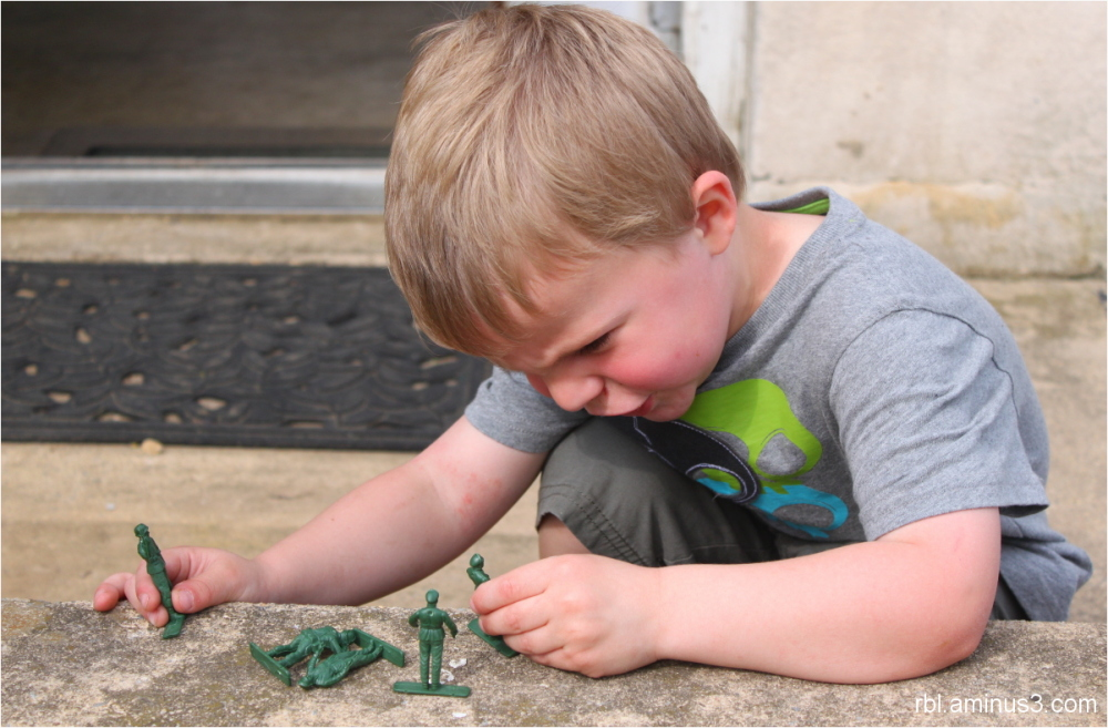 child playing with army men