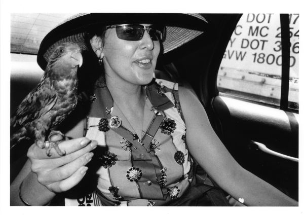 bizarre lady with bird in taxi back seat