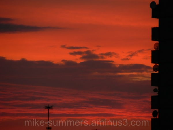 Sunset over London with towerblock and Sky dishes