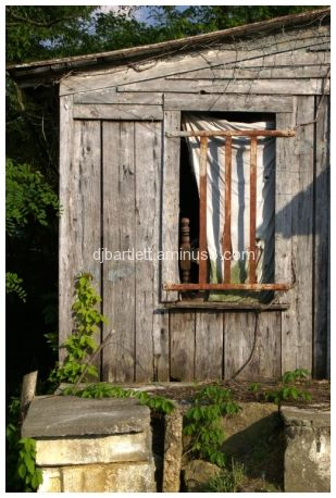 Window with bed frame and curtain, abandoned house