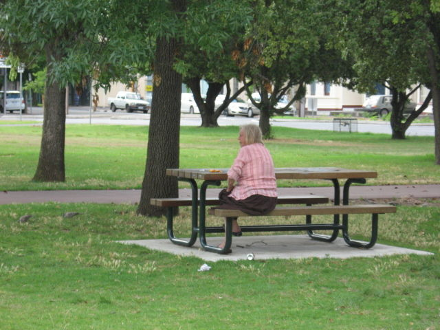 An old homeless lady in the park.
