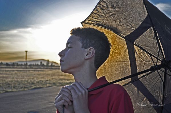 An HDR photo of a boy holding an umbrella