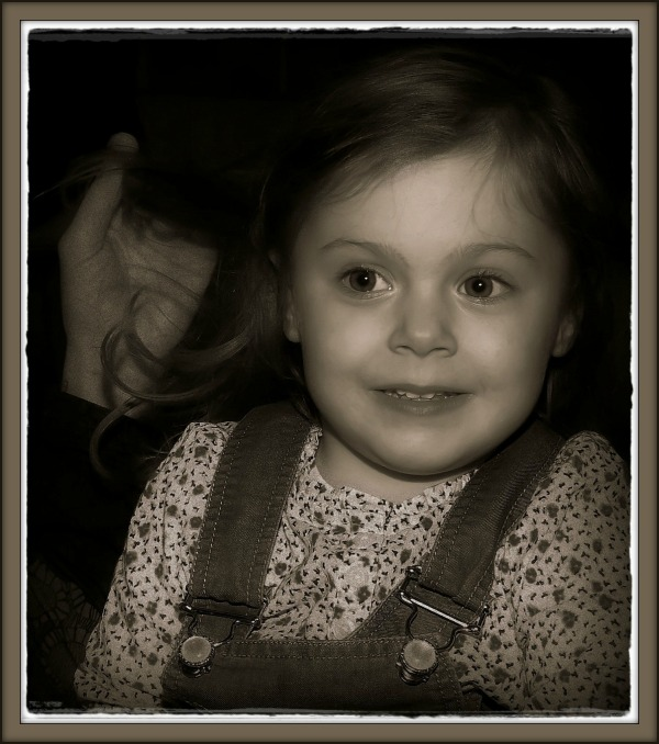 emilia, 38 months old, timid smile, hand