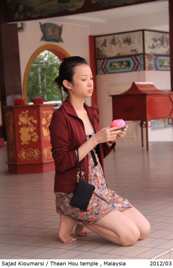 chinese woman prays in thean hou temple, malaysia