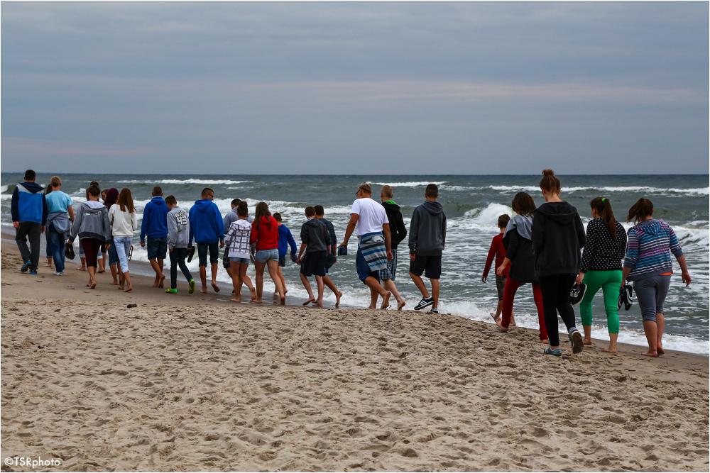 crowd people walk beach sea waves