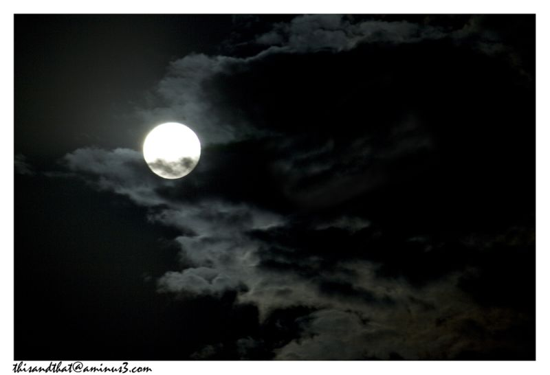A rising moon on a cloudy night