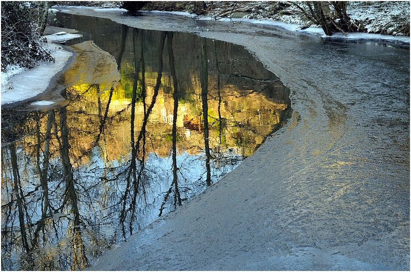 Reflets du paysage ensoleillé et la rivière gelée