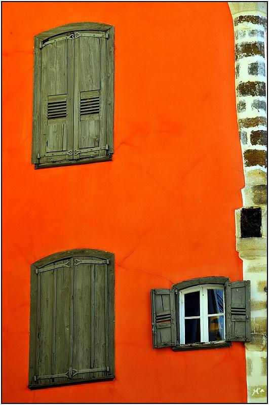 Sur la façade rouge trois fenêtres