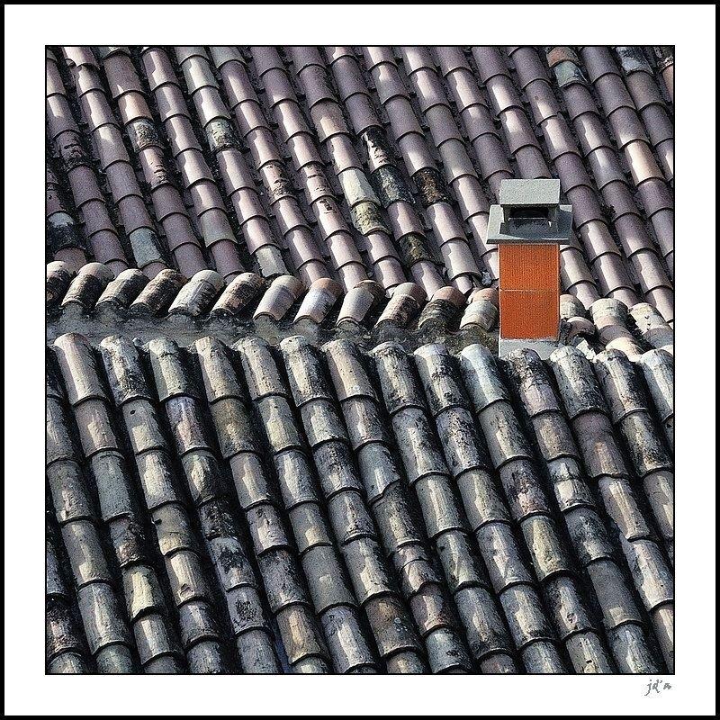 Une cheminée orange sur un toit