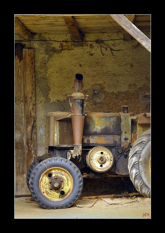 Un très vieux tracteur dans une remise.