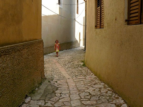 girl walking in a street of Vrbnik Croatia
