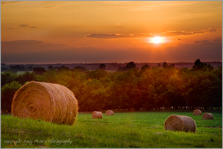 Rural Missouri sunrise over field of hay bales