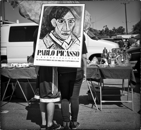 couple at swap meet hold picasso poster