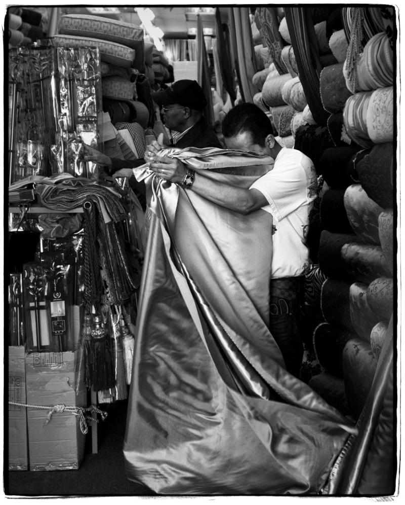 man folding fabric