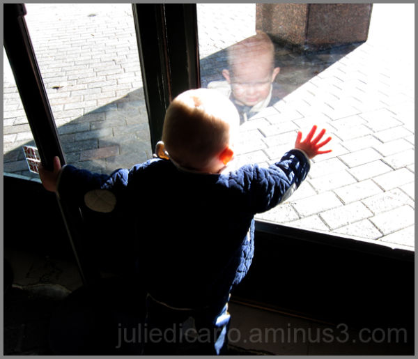 Child looking out glass door