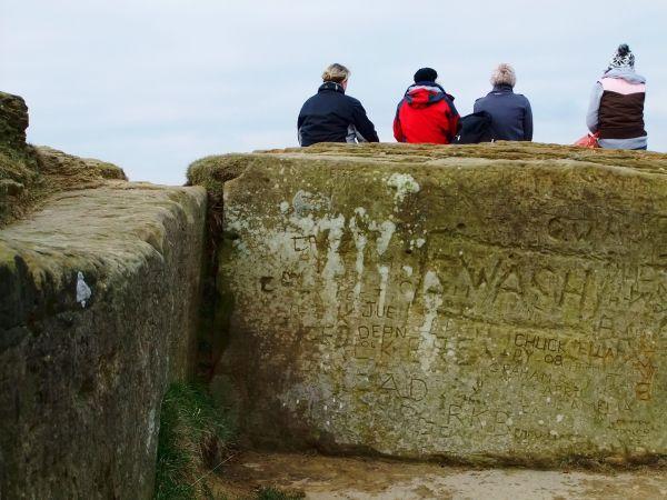 walkers resting on graffiti scored rock