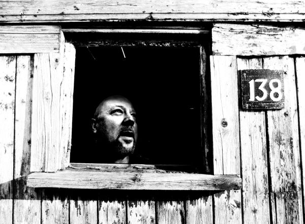 man looking out of the window of an old wood shed