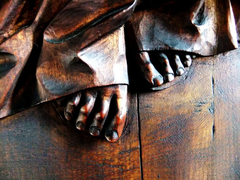 A carved oak relief of Christ's feet