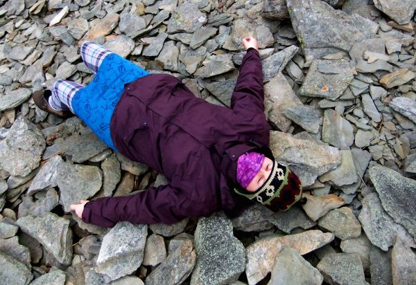 female hiker lying down among rocks